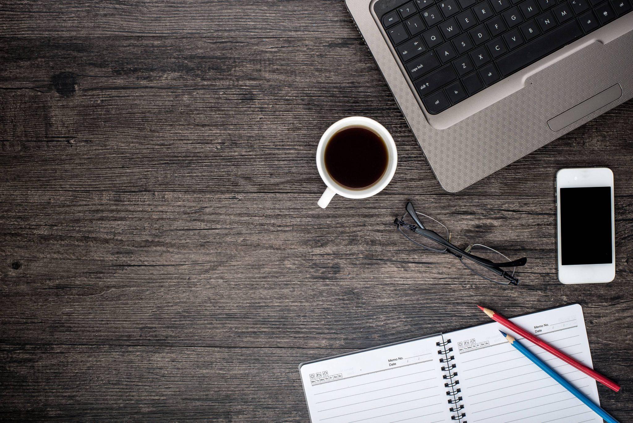 Kontorbord med kaffe, telefon, computer og notesbog