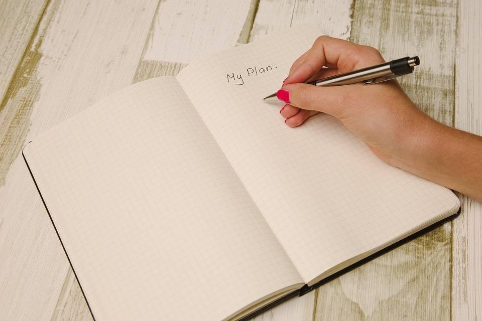 """Hånd der skriver """"min plan"""" i notesbog"""