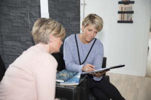 to siddende kvinder kigger på et stykke papir