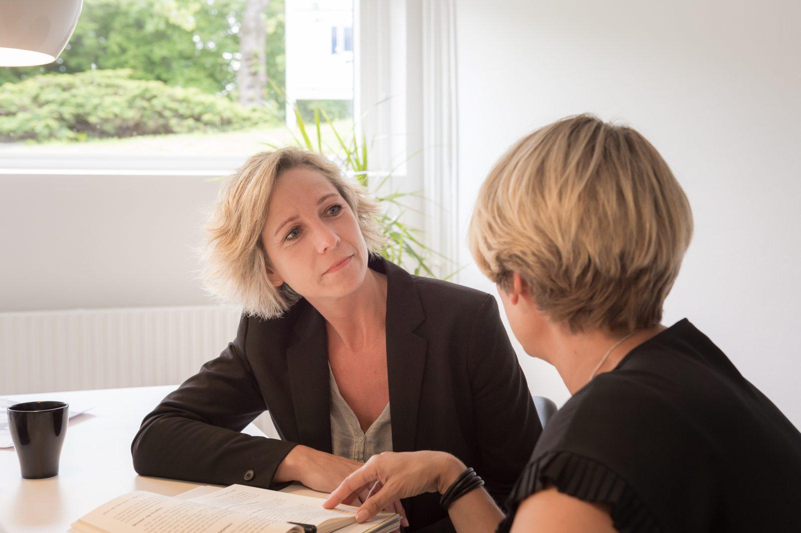 To kvinder ved et bord med en åben bog har en samtale