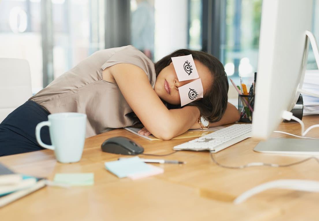 Kvinde hviler på bord med et stykke papir på hvert øjne, hvor der er tegnet åbne øjne