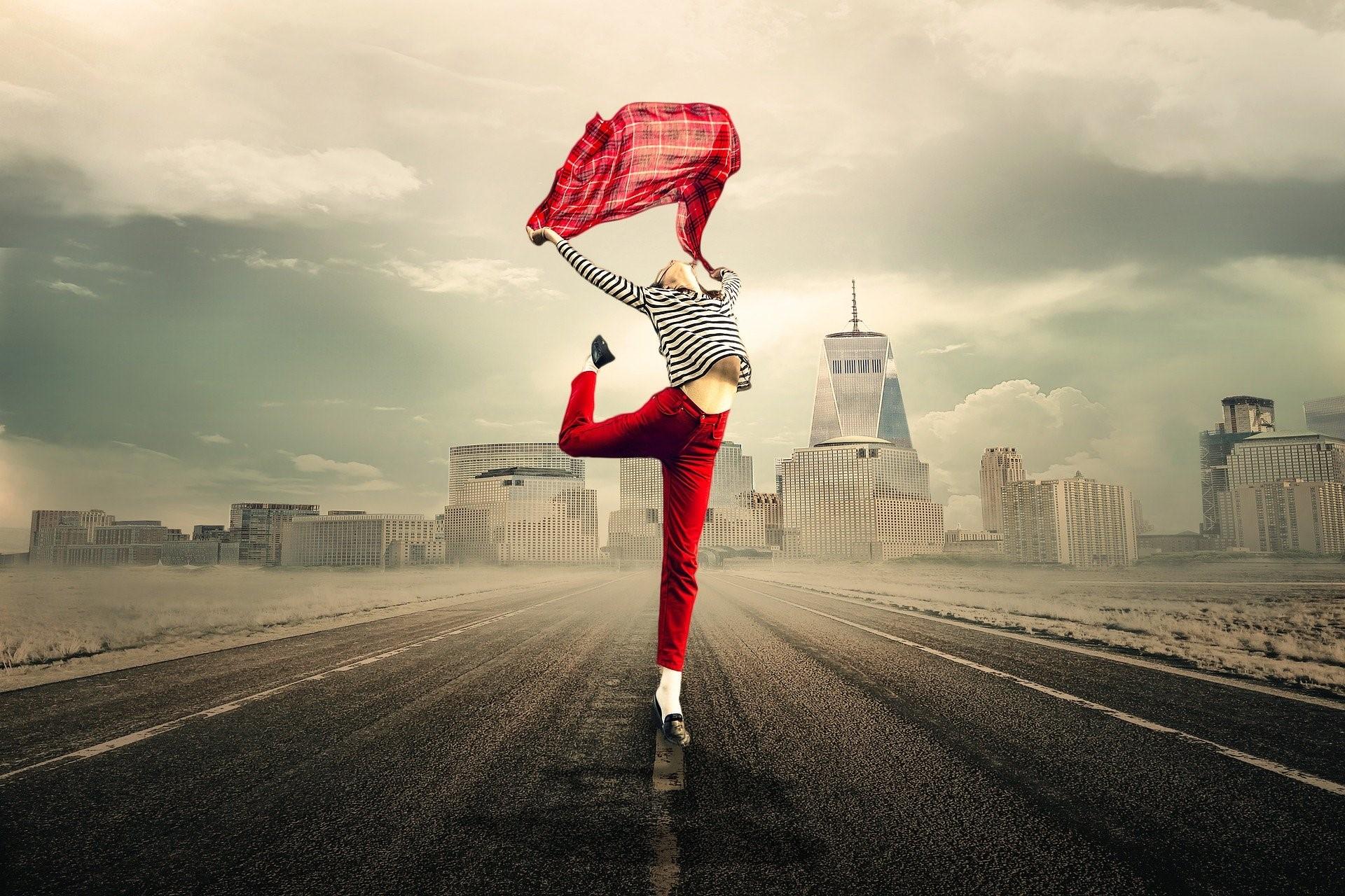 Kvinde iført rødt laver balletlignende dans på vej med by i baggrunden