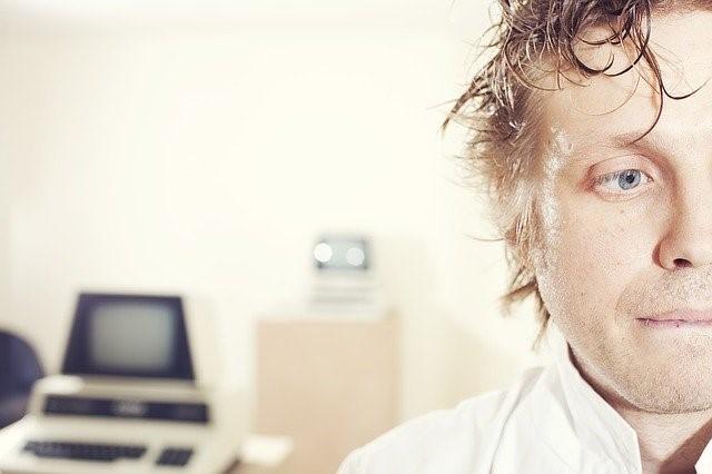 Halvdelen af en mands hoved med vådt og uglet hår med sløret baggrund